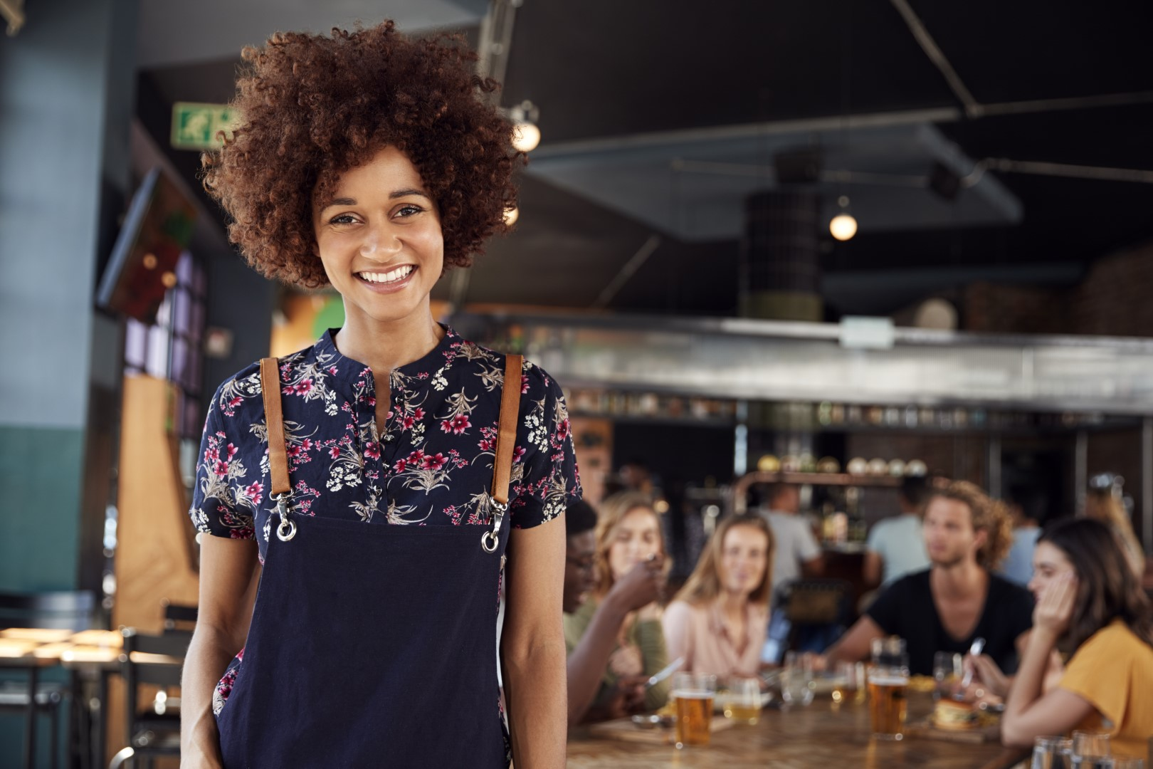 Portrait Of Waitress Serving In Busy Bar Restaurant
