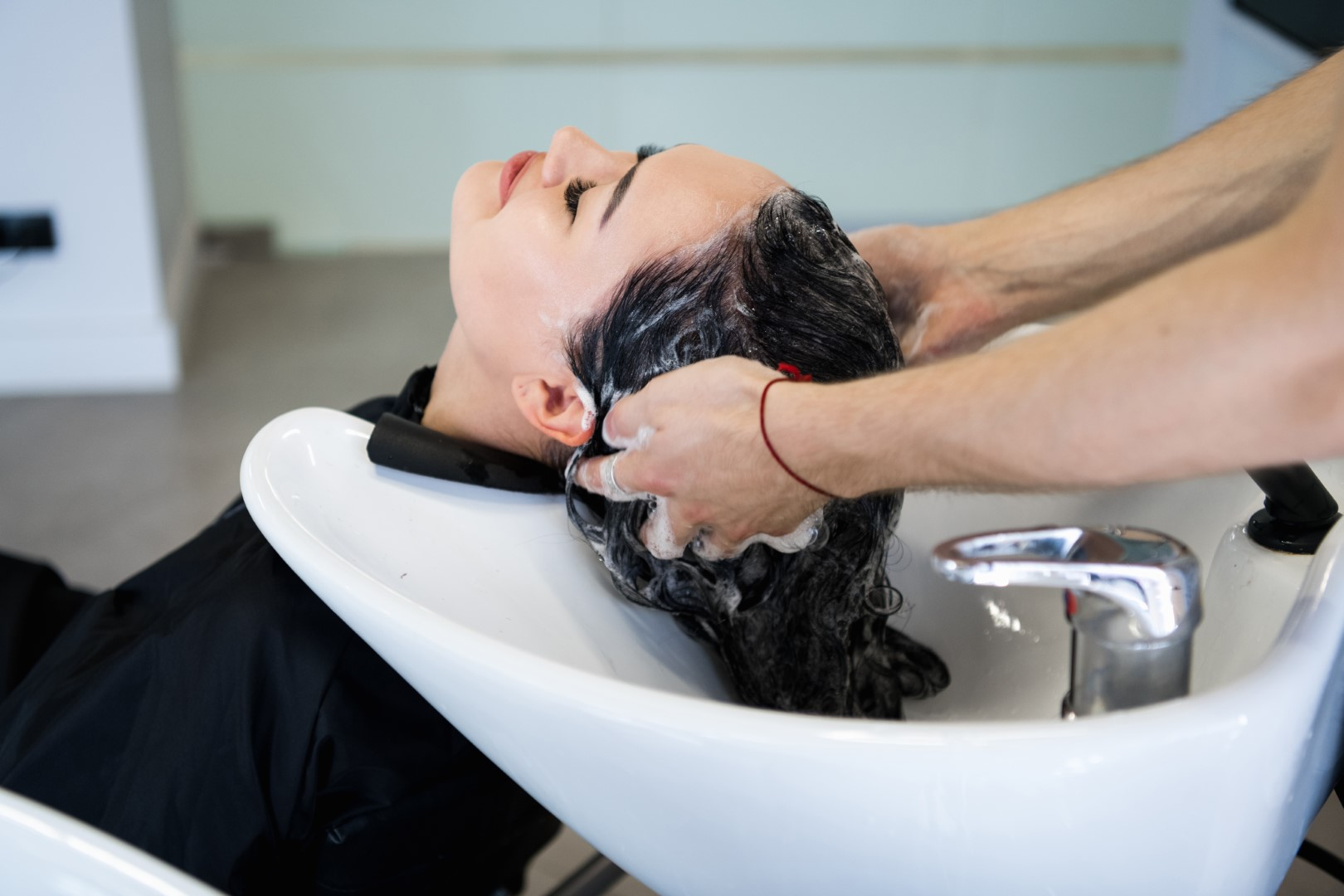 Beautiful brunette washes hair in a beauty salon